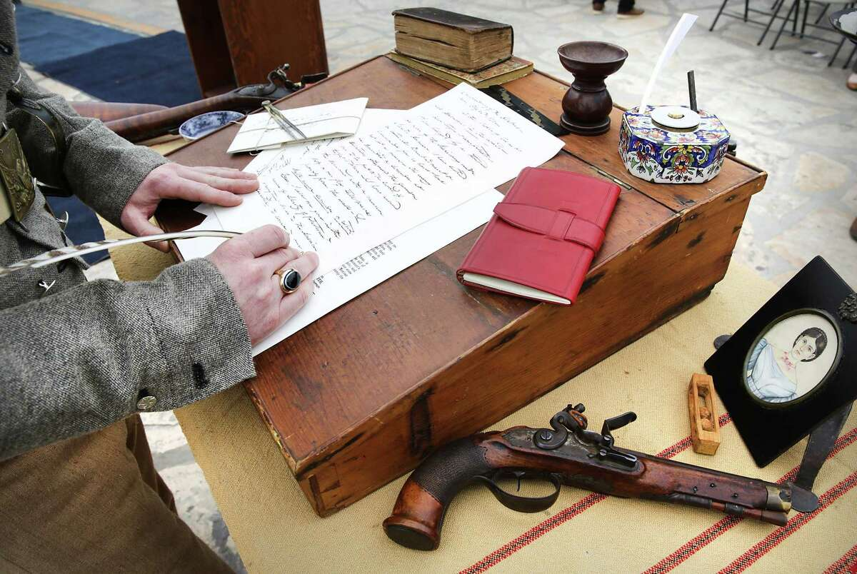 """Erik McBroom, portraying William B. Travis, signs a copy of his famous """"victory or death"""" letter, during a re-enactment at the Alamo on Monday morning. Attended by about 200 people, including a group of schoolkids, the event is part of a series of demonstrations and reenactments marking the 13-day siege and Battle of the Alamo in 1836."""