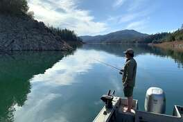 Jeremy Keyston casts for bass at Shasta Lake, where warm, calm days have felt like spring, the picture this week at many lakes in California
