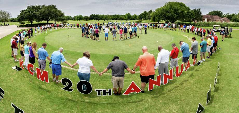 Players pray before last year's golf tournament benefiting Katy Christian Ministries. Photo: Courtesy Photo