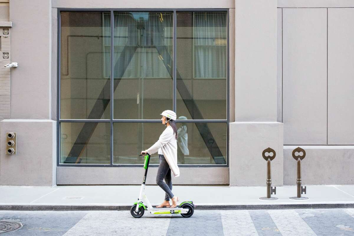 Riding a Lime scooter down the street.