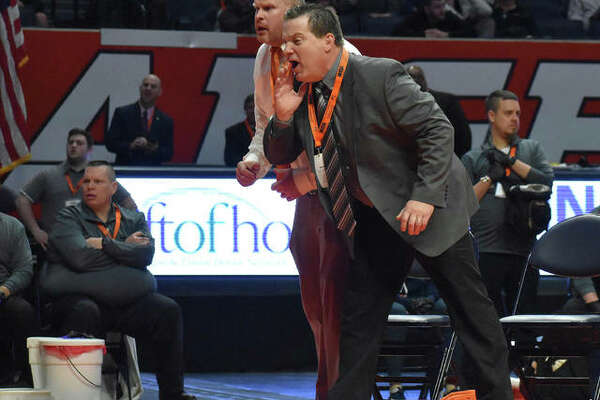 Edwardsville coach Jon Wagner, front, and assistant coach Doug Heinz shout out instructions during the 285-pound championship match at the Class 3A state tournament.
