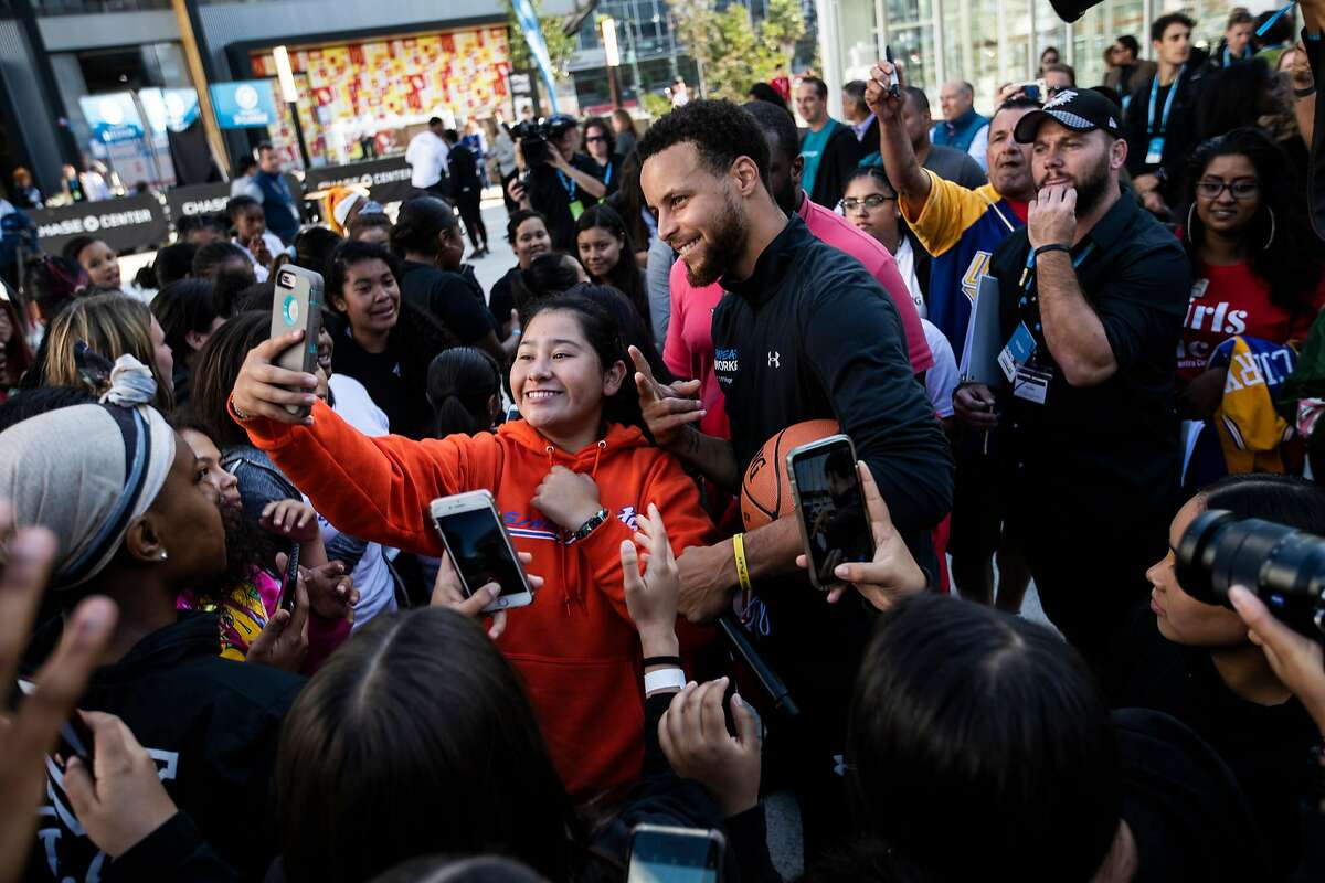 Attendees encircle Stephen Curry of the Golden State Warriors for a photo after a Sweatworking event on girls� equity & equality and financial health at Chase Center Plaza in San Francisco, Calif. on Wednesday, Sept. 4, 2019.