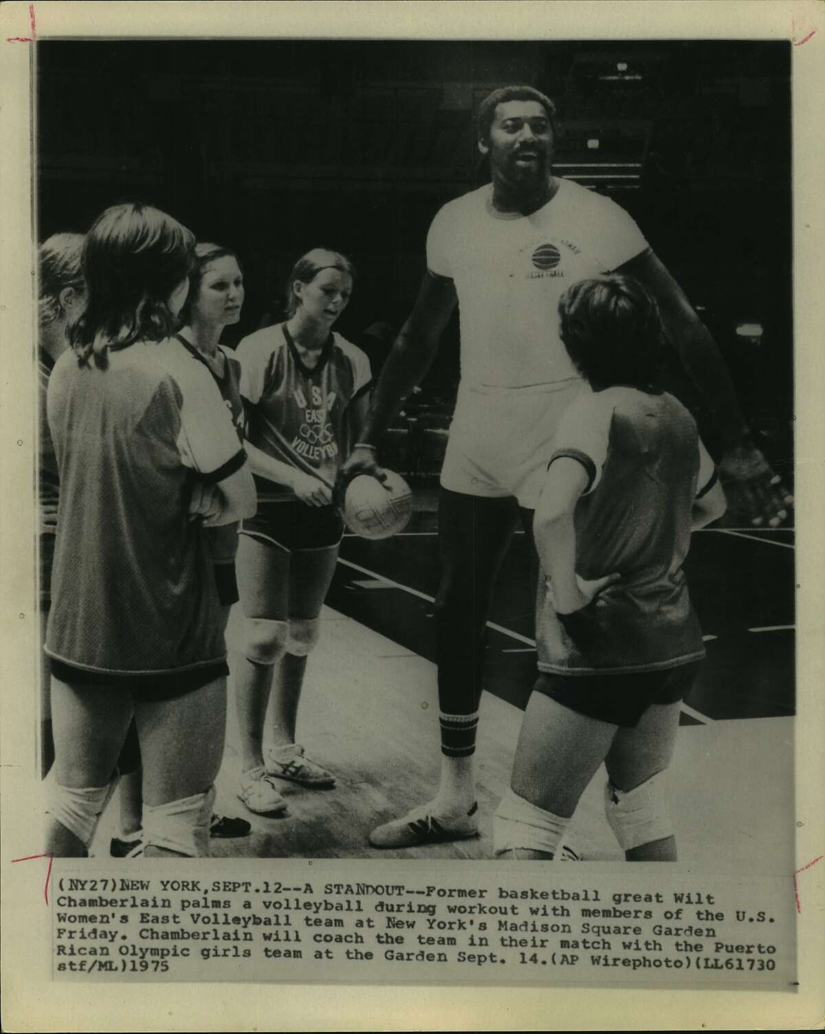 A Standout--former basketball great Wilt Chamberlain palms a volleyball during work out with members of the US Women's East Volleyball team at New York's Madison Square Garden Friday. Chamberlain will coach the team in their match with Puerto Rican Olympic girls team at the garden September 14.