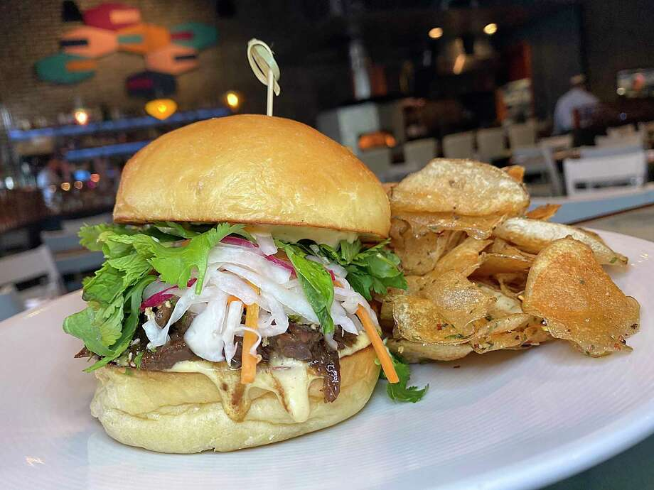 The Far Eastsider sandwich incorporates bulgogi-style beef cheeks, vinegar slaw, herb salad and golden beet aioli on a housemade bun with freshly made potato chips at Full Belly Cafe and Bar. Photo: Mike Sutter /Staff