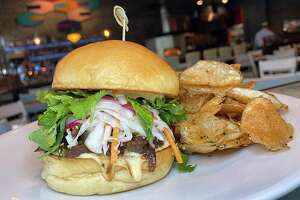 The Far Eastsider sandwich incorporates bulgogi-style beef cheeks, vinegar slaw, herb salad and golden beet aioli on a housemade bun with freshly made potato chips at Full Belly Cafe and Bar.