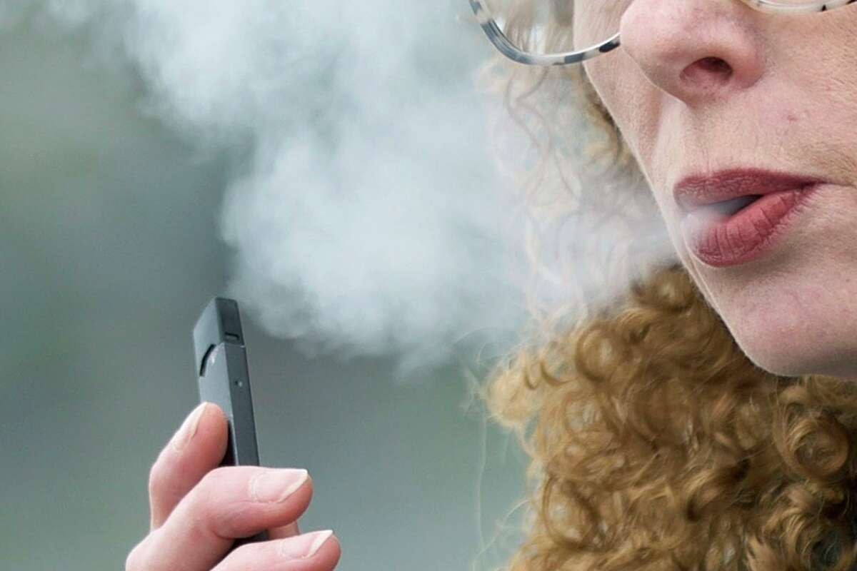 A woman exhales while vaping from a Juul pen e-cigarette.