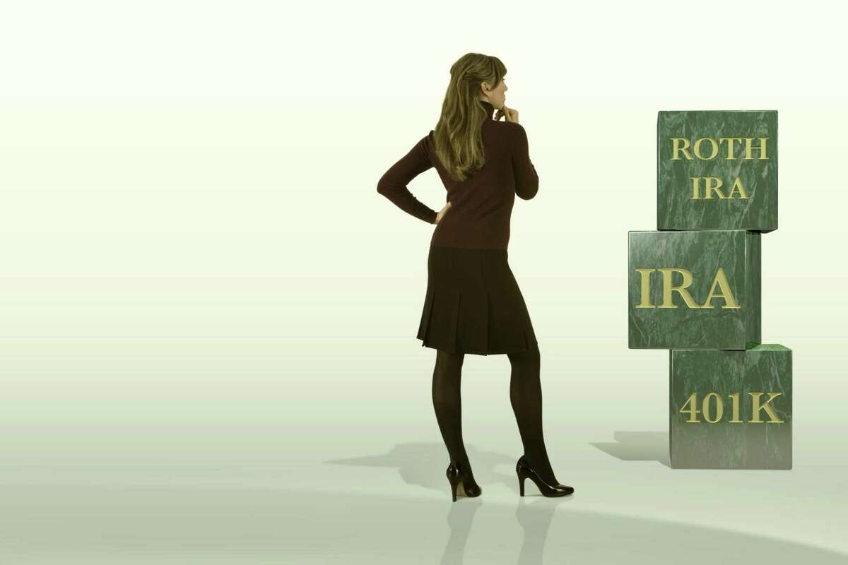 A businesswoman examines blocks for Roth IRAs, IRAs, and 401ks.