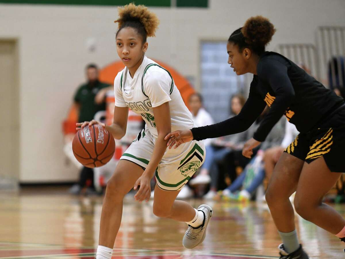 Spring freshman guard Kierra Merchant, left, works the ball up the court against Klein Oak sophomore guard Jasmine Clark, right, during the first quarter of their Region II-6A UIL Girls Basketball Bi-District playoff matchup at The Woodlands High School on Feb. 18, 2020.