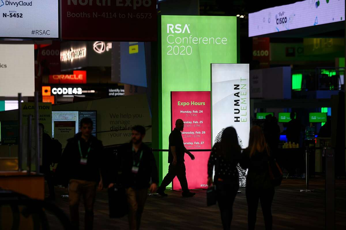 RSA Conference 2020 attendees pass signs at Moscone Center on Monday, Feb. 24, 2020, in San Francisco.