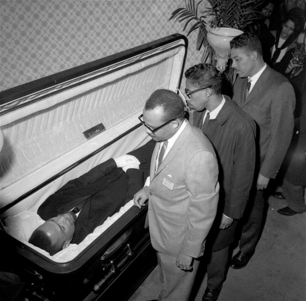 File - In this Feb. 24, 1965, file photo, the body of Malcolm X, black nationalist leader who was slain February 21, 1965, at a rally of his organization, is viewed by newsmen at the Unity Funeral Home, Eighth Avenue and 126th Street in New York City.