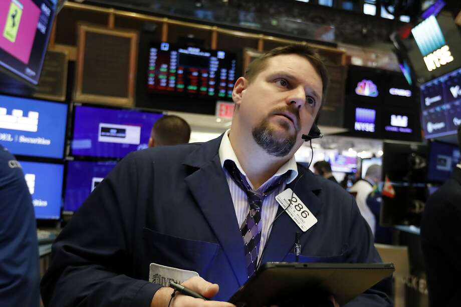 Trader Michael Milano works on the floor of the New York Stock Exchange, where things were not exactly cheery Monday. Most stocks fell sharply. Photo: Richard Drew / Associated Press