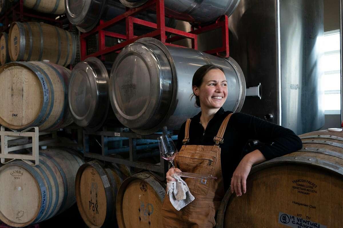 Martha Stoumen stands in front of her wine barrels where she works in Sebastopol, California.