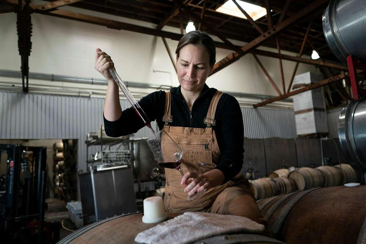 Martha Stoumen pulls wine out of one of her barrels where she works in Sebastopol, California.