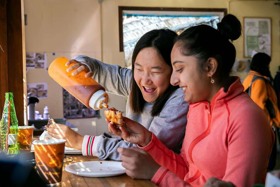 Sixteen-year-old Rose Liu helps Simran Gupta, also 16, put some sauce on her spinach and cheese pastry at Sultan Bakery Grill in San Jose. Photo: LiPo Ching / Special To The Chronicle
