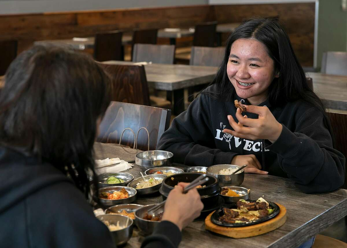 Princess Quintal, 17, right, and Jackie Gatmen, visiting from Guam, eat lunch at Danbi Korean Restaurant on Tuesday, Feb. 18, 2020 in San Jose, Calif.