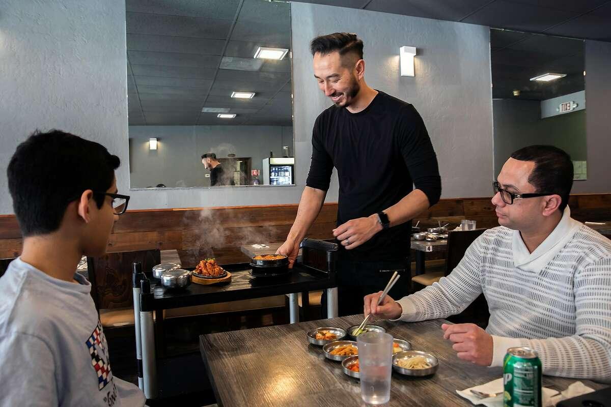 Co-owner Robert Turner, serves lunch to Tony Kumar, right, and Sunny Kumar, 15, at Danbi Korean Restaurant on Tuesday, Feb. 18, 2020 in San Jose, Calif.