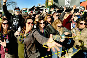 Crystal Brown of Wood River reaches out to catch beads during the Wordi Gras parade in Worden Saturday.