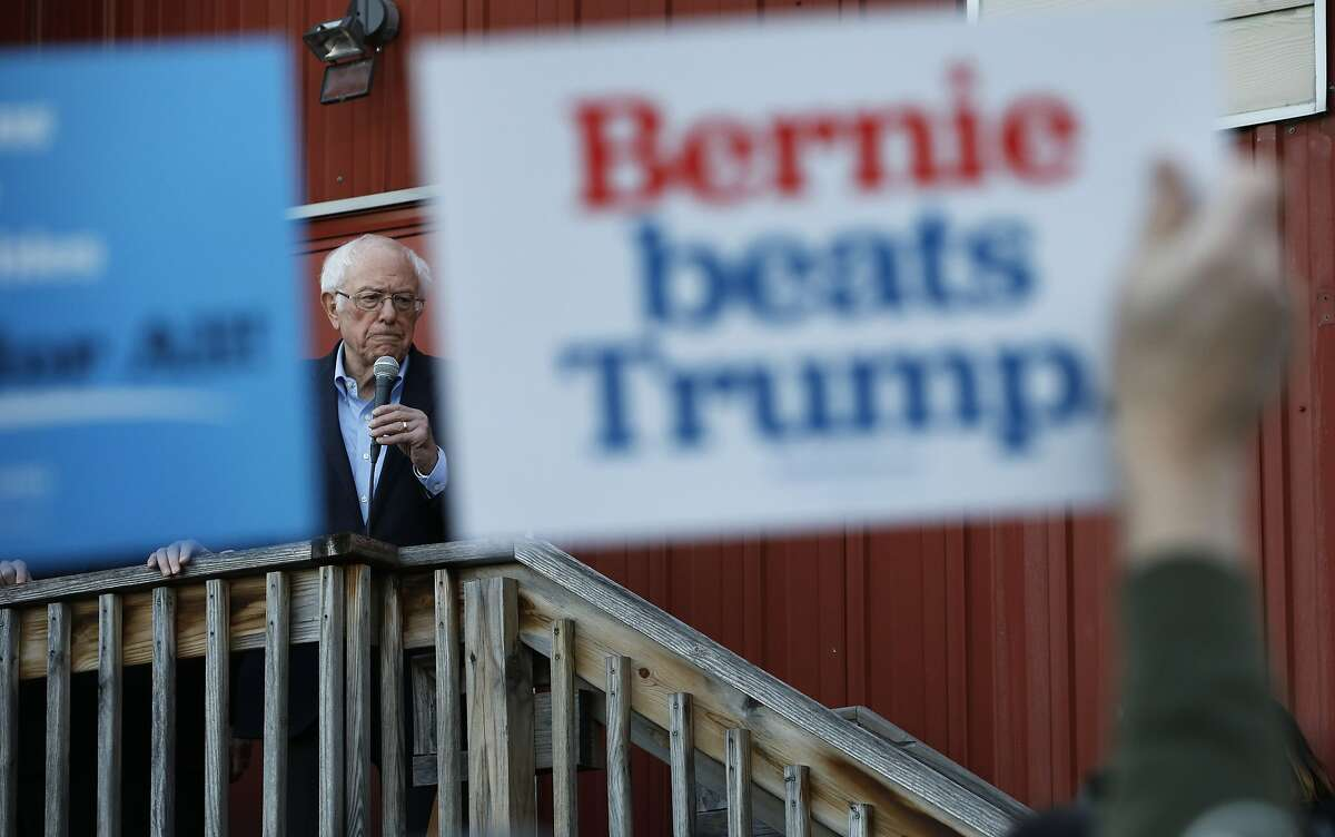"""A person in the audience holds up a sign that reads """"Bernie beats Trump"""" as Democratic presidential candidate Sen. Bernie Sanders, I-Vt., speaks to an overflow crowd at a Super Bowl watch party campaign event, Sunday, Feb. 2, 2020, in Des Moines, Iowa. (AP Photo/John Locher)"""