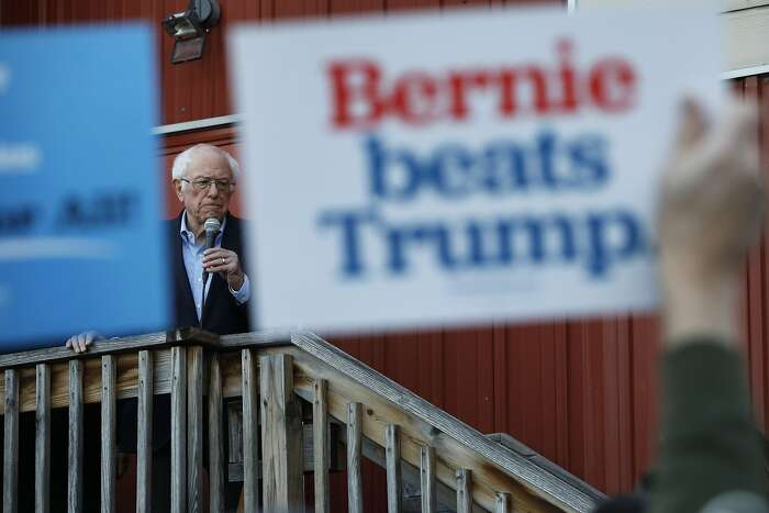 "A person in the audience holds up a sign that reads ""Bernie beats Trump"" as Democratic presidential candidate Sen. Bernie Sanders, I-Vt., speaks to an overflow crowd at a Super Bowl watch party campaign event, Sunday, Feb. 2, 2020, in Des Moines, Iowa. (AP Photo/John Locher)"