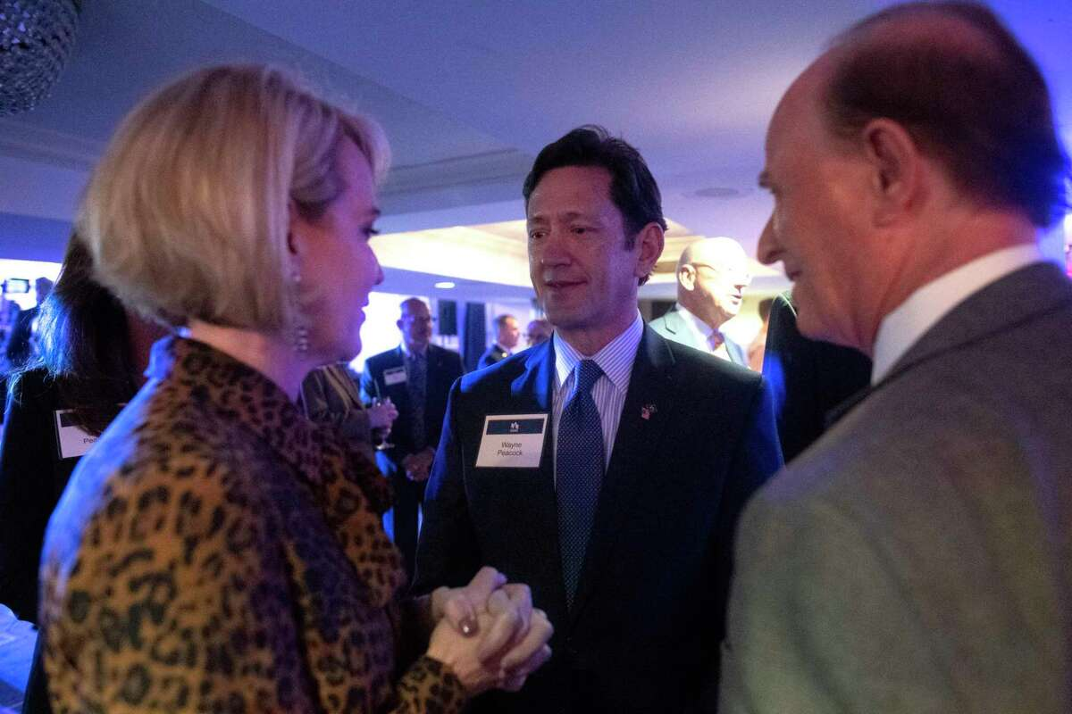 USAA's new CEO, Wayne Peacock, center, converses with public relations executive Trish DeBerry, left, and County Judge Nelson Wolff during a reception at the Sheraton Gunther hotel on Feb. 24.