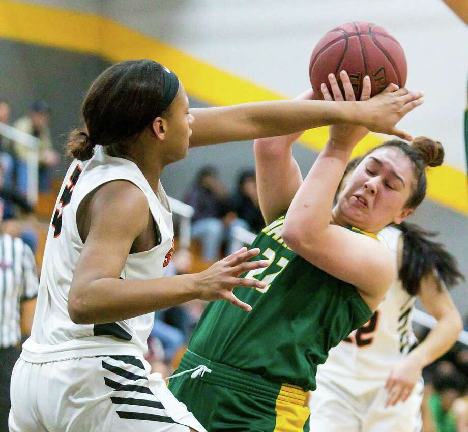 Shelton's Clarissa Pierre blocks the shot attempt by Hamden's Yariliz Santiago during their SCC semifinal Monday night in Milford. Photo: John Vanacore / For Hearst Connecticut Media / (c)John H.Vanacore
