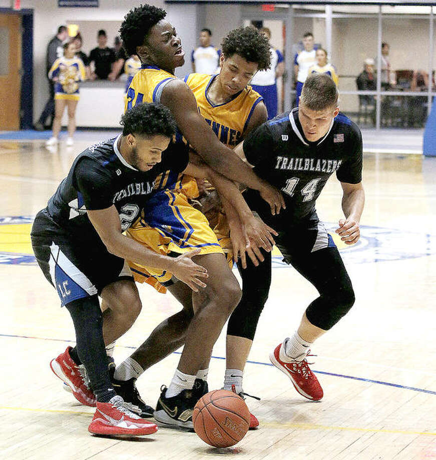 Vincennes University's Chinedu Okanu and Craig Porter, middle, along with Lewis and Clark's Ulysses Delayney, left, and Amandas Urkis (14) charge after a loose ball Monday night at Vincennes.