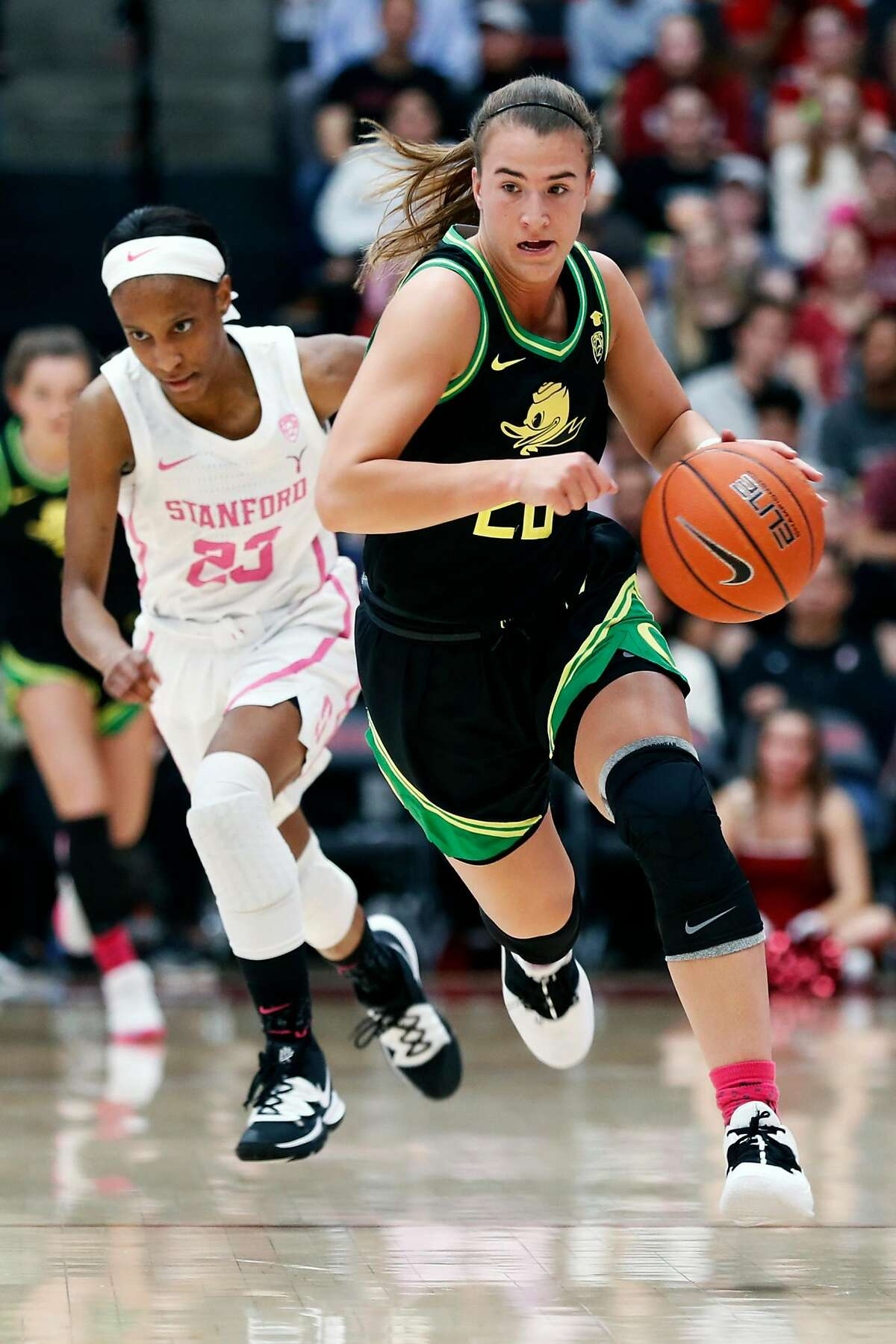 """Stanford's Kiana Williams trails Oregon""""s Sabrina Ionescu up the court during Pac 12 women's basketball game at Maples Pavilion in Stanford, Calif., on Monday, February 24, 2020."""