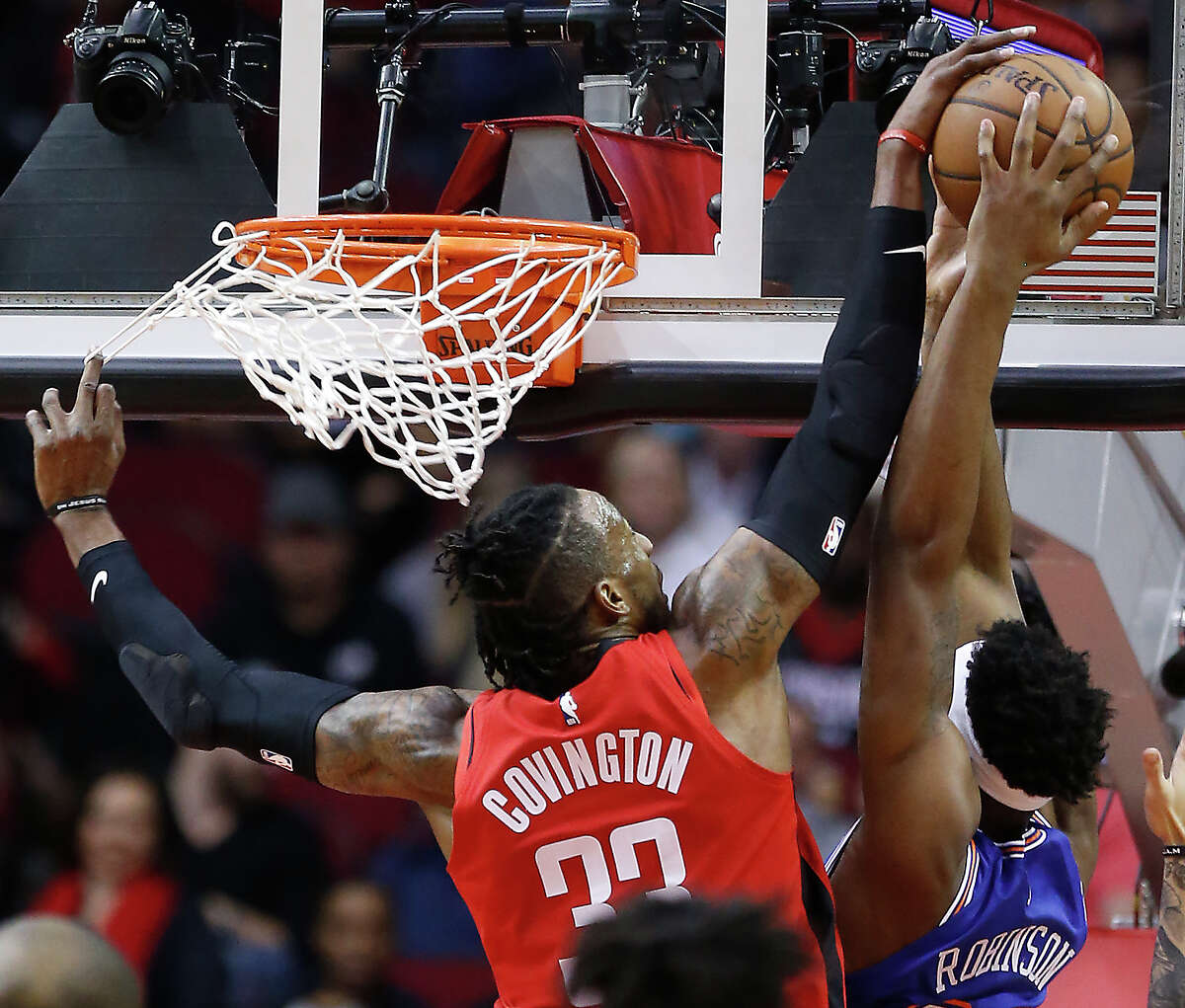 Houston Rockets forward Robert Covington (33) goes up for a block on a shot by New York Knicks center Mitchell Robinson (23) and is called for a foul during the first half of an NBA basketball game on Monday, Feb. 24, 2020, at Toyota Center in Houston.