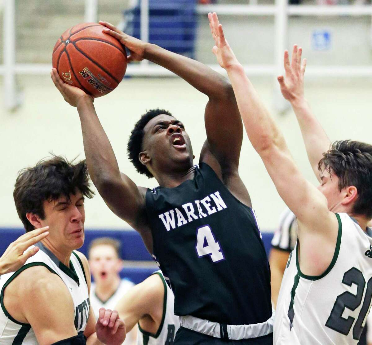 Zane Elmore battles in the lane to put up a shot against Will Carsten, left, and Zach Lee as Warren plays Reagan in boys basketball playoff action at Taylor Field House on Feb. 24, 2020.