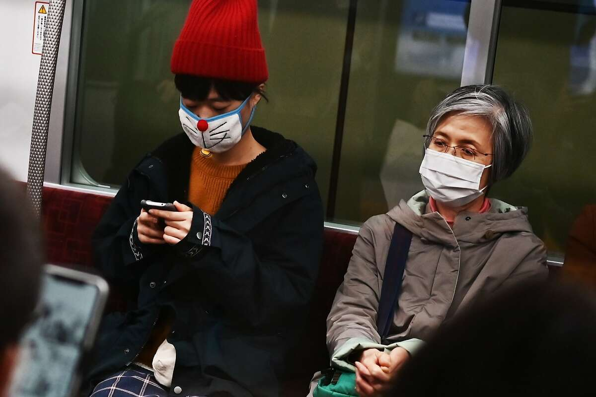 People wearing face masks travel on a train in Tokyo on February 25, 2020. - Japan has more than 150 cases of the COVID-19 coronavirus and five have died. Four of those deaths were passengers who had been on the cruise ship Diamond Princess, quarantined off in Yokohama, where the number of infections is over 690. (Photo by CHARLY TRIBALLEAU / AFP) (Photo by CHARLY TRIBALLEAU/AFP via Getty Images)