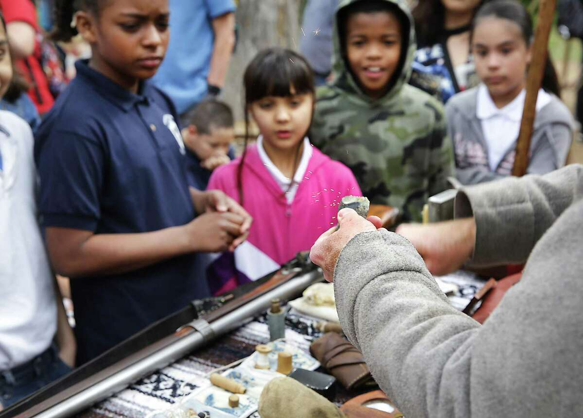 Esparza Elementary students A'miyah Simmons, from left, Amber Apolinar, Deonta Corley and Annabelle Casarez learn how to start a fire with flint.