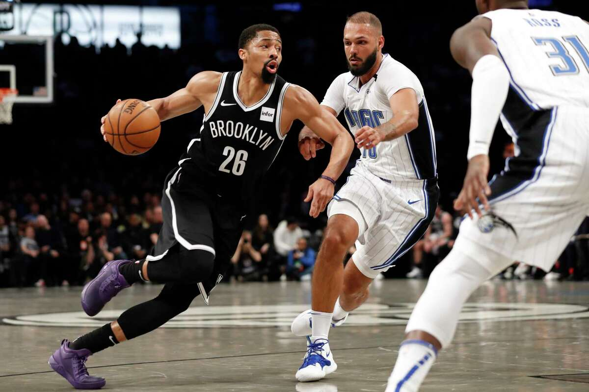 Brooklyn Nets guard Spencer Dinwiddie (26) drives around Orlando Magic guard Evan Fournier (10) during the first half of an NBA basketball game Monday, Feb. 24, 2020, in New York. Magic guard Terrence Ross (31)watches. (AP Photo/Kathy Willens)