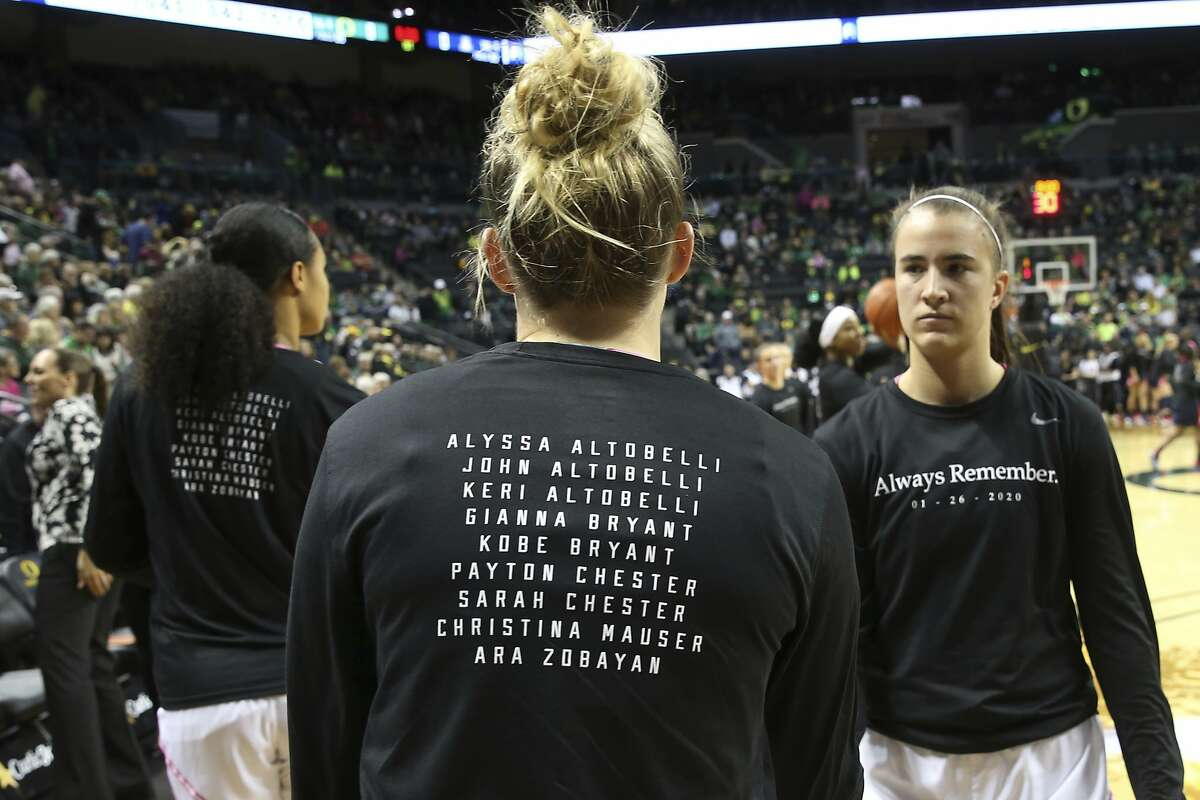 Oregon's Satou Sabally, left, Holly Winterburn and Sabrina Ionescu, right, wear T-shirts honoring the people lost in the helicopter crash along with Kobe Bryant, before the team's NCAA college basketball game against Arizona in Eugene, Ore., Friday, Feb. 7, 2020. (AP Photo/Chris Pietsch)