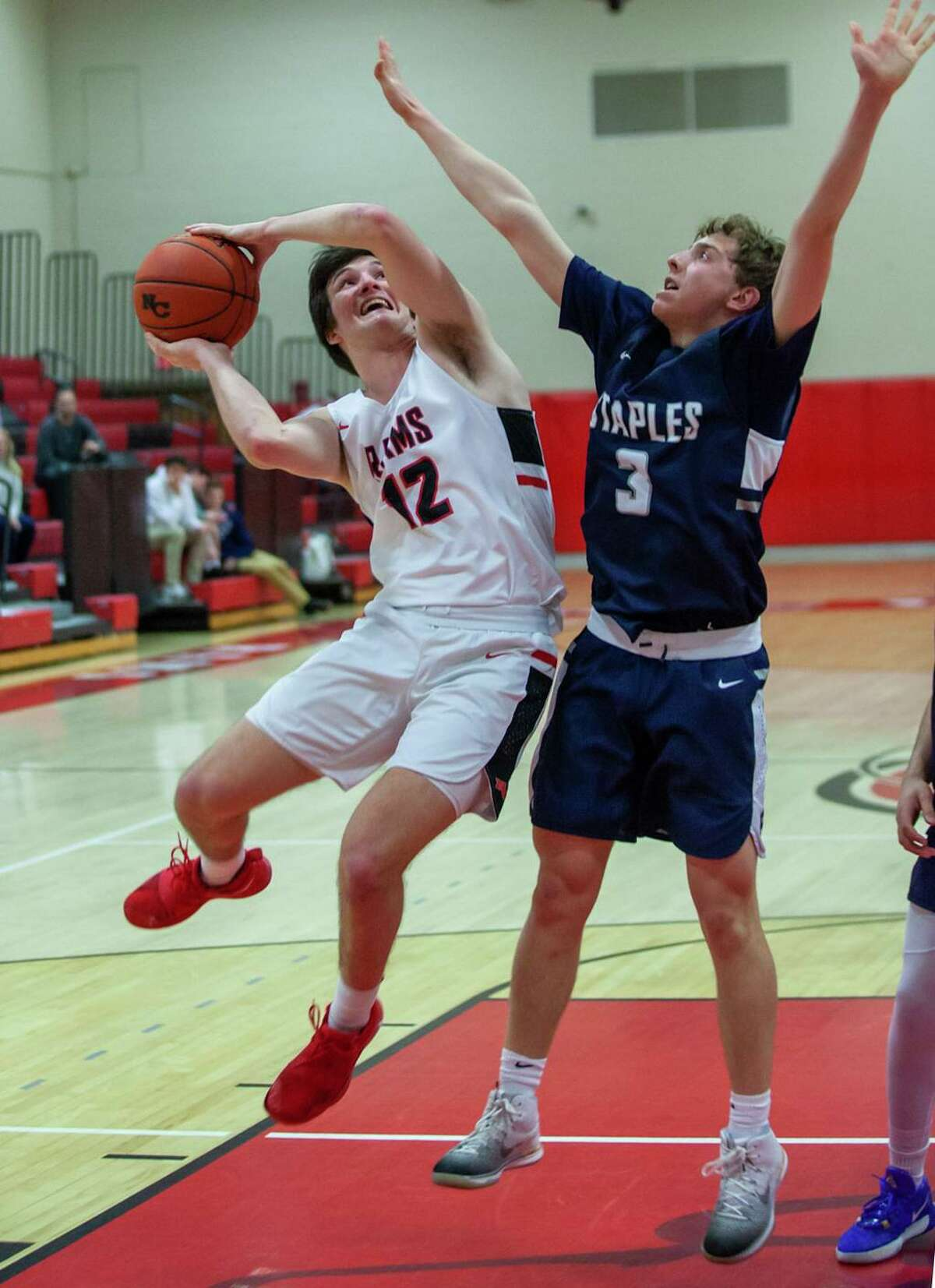 New Canaan's Christian Sweeney (12) goes up for a shot, while Staples' Derek Sale (3) defends during a boys basketball game at New Canaan High School on Monday, Feb. 24, 2020.