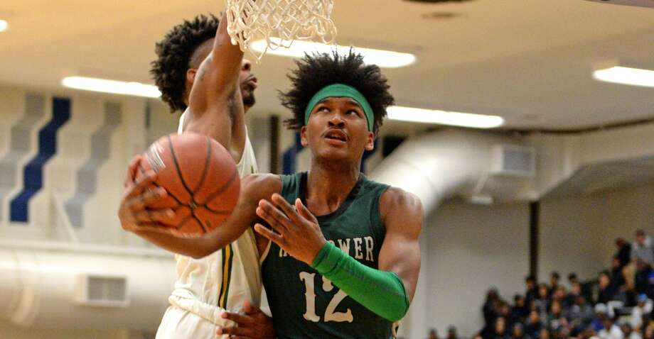 Bryce Griggs (12) of Hightower drives to the basket during the first half of a 5A Region III Bi-District playoff game between the Hightower Hurricanes and the Sharpstown Apollos on Monday, February 24, 2020 at Butler Fieldhouse, Houston, TX. Photo: Craig Moseley/Staff Photographer