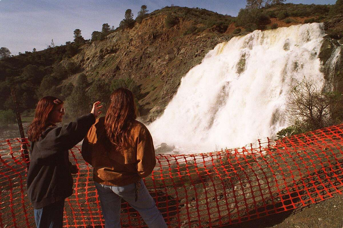 SPILLWAY/C/23FEB96/CD/CASTILLO Katrina Kunkel (13) brushes away spray from her mother Marleen's (cq) hair while the pair watches the spillway release of excess water from Anderson Reservoir in Morgan Hill, California. Eight of the ten reservoirs in Santa Clara County are making releases this week. PHOTO BY STEVE CASTILLO/FOR THE CHRONICLE