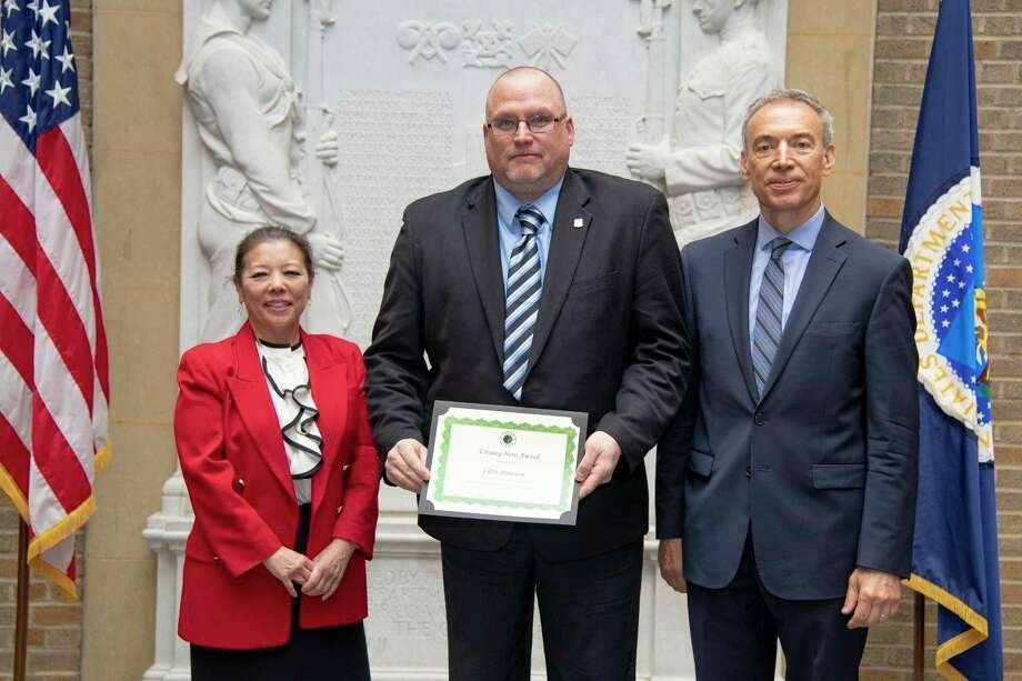 Chris Peterson (center) receives the USDA Unsung Hero Award last year for having demonstrated momentous leadership, immediate action, and courageous behavior in the course of his duties. (Courtesy Photo/USDA)