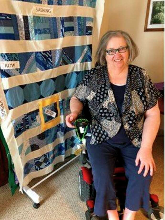 Peggy Zimmermann poses with a sample quilt showing different types of quilting methods. (Photo provided)