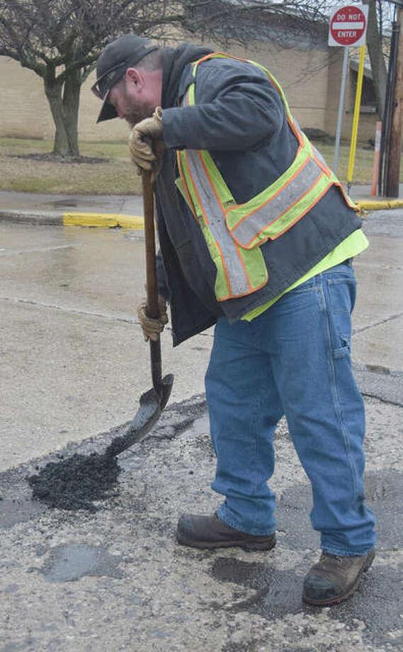 Jacksonville Street Department worker Brett Hartke fills a pothole Monday on South West Street. Photo: Rochelle Eiselt | Journal-Courier