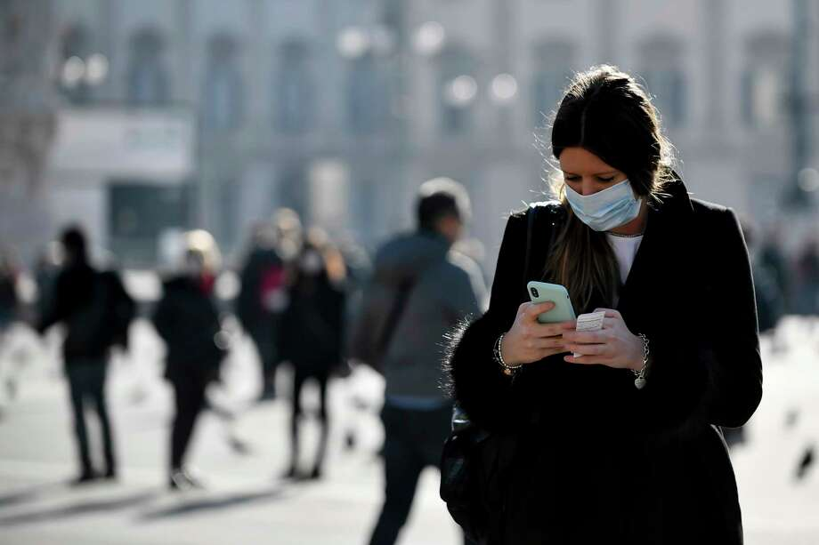 A woman wearing a sanitary mask looks at her phone in Milan, Italy, Monday, Feb. 24, 2020. At least 190 people in Italy's north have tested positive for the COVID-19 virus and four people have died, including an 84-year-old man who died overnight in Bergamo, the Lombardy regional government reported. (Claudio Furlan/Lapresse via AP) Photo: Claudio Furlan, AP / LaPresse