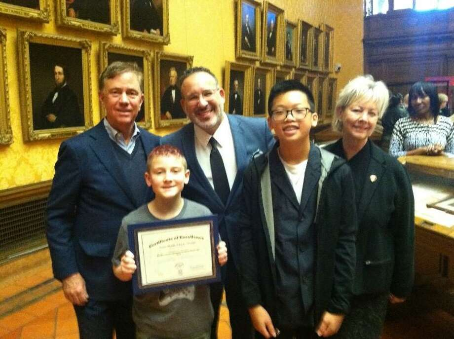 Aiden Graham and David Ke were named the top readers from Amity Middle School in Orange in the Governor's Summer Reading Challenge. Aiden and David traveled to Hartford to receive their recognition certificates on behalf of Amity Middle School in Orange. The school was recognized for having the highest number of books read by participating students in middle school. In the back ro, from left, are Gov. Ned Lamont; Dr. Miguel A. Cardona, Commissioner of Education; Dr. Marie McPadden, Amity Regional School District No. 5 Director of Curriculum and Staff Development; (front row) Aiden Graham; and David Ke. Photo: Marie McPadden / Contributed Photo