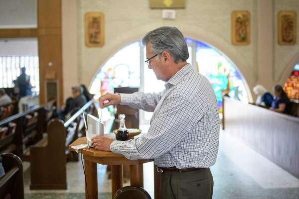 Roland Davila uses the DipJar, a card-reading donation device, during Sunday Mass at St. Paul Catholic Church. St. Paul added the device several months ago for parishioners and visitors who don't carry cash or checks for the collection basket.