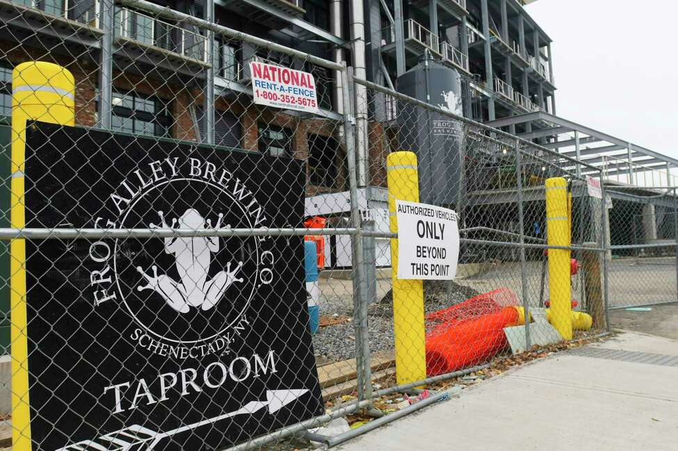A view of a sign for Frog Alley Brewing along the construction fencing on Tuesday, Feb. 25, 2020, in Schenectady, N.Y. (Paul Buckowski/Times Union)