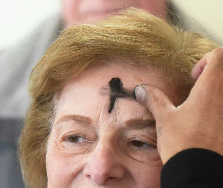 "Stamford's Joyce Mirizio receives ashes for Ash Wednesday at the Stamford Lincoln Ford dealership in Stamford, Conn. Wednesday, Feb. 14, 2018. Christians celebrated Ash Wednesday to mark the start of Lent, which is six weeks of repentance before Easter. Norwalk's St. Matthew Church made a stop at the Lincoln Ford dealership in Stamford to offer ""ashes on the bus,"" while also stopping by different places in Norwalk, Wilton and Southport. The United Methodist Church of New Canaan had services for Ash Wednesday, February 26, 2020. Photo: Tyler Sizemore / Hearst Connecticut Media / Greenwich Time"