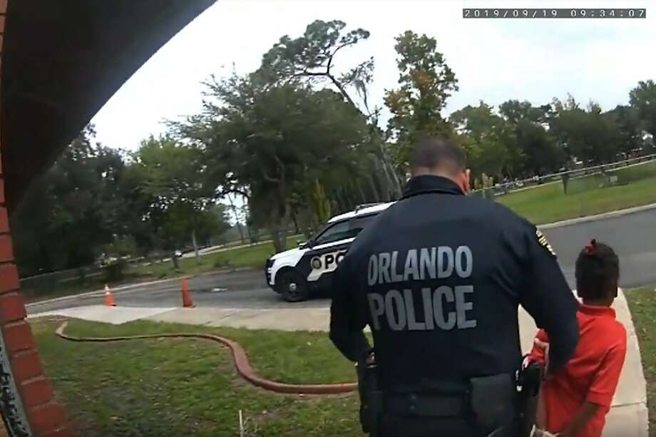In this image taken from Sept. 19, 2019, Orlando Police Department body camera video footage, Orlando Police Officer Dennis Turner leads 6-year-old Kaia Rolle away after her arrest for kicking and punching staff members at the Lucious & Emma Nixon Academy Charter School in Orlando, Fla. Turner was fired shortly after the arrest for not getting the approval of a watch commander to arrest someone younger than 12. (Orlando Police Department/Orlando Sentinel via AP) Photo: Associated Press