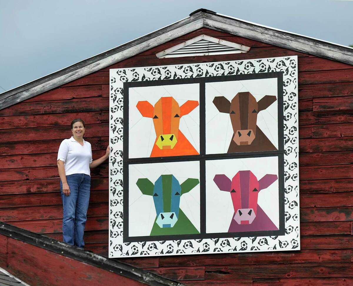 The Barn Quilt Trail in New Milford is looking to expand to include 10 new barn sites, on top of the original eight sites. Above, Susan Bailey, whose family owns Harris Hill Farm in New Milford, stands on the roof of a barn near a quilt painting of cows in 2017.