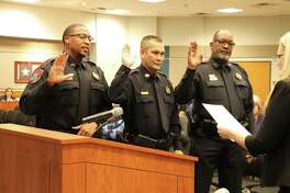 Eric Chimney, from left, Jame Mitchell and Ryan Pickett are sworn in as new Katy Independent School District police officers at the Board of Trustees meeting on Monday, Feb. 24, at the Education Support Complex.