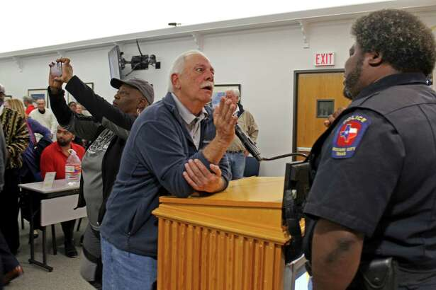An upset resident talks with a Missouri City Police officer after a special meeting held Tuesday, Feb. 24, when Mayor Yolanda Ford and the City Council voted 4-to-3 to terminate the contract of City Manager Anthony Snipes residents.
