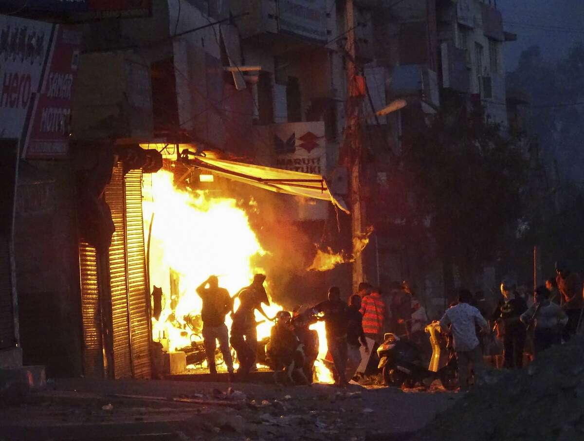 A shop is set on fire during violence between two groups in New Delhi, India, Tuesday, Feb. 25, 2020. At least 10 people were killed in two days of clashes that cast a shadow over U.S. President Donald Trump's visit to the country. (AP Photo)