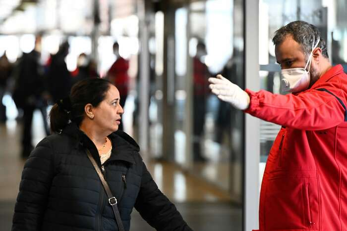 A member of the Fire safety and personal assistance (Service de securite incendie et d'assistance � personnes - SSIAP) gives indications to people at the train and bus station Lyon Perrache after marking a security zone, following the blockage of a bus coming from Milan due to suspected COVID-19 the novel coronavirus on board, in Lyon, on February 24, 2020. (Photo by JEAN-PHILIPPE KSIAZEK / AFP) (Photo by JEAN-PHILIPPE KSIAZEK/AFP via Getty Images)